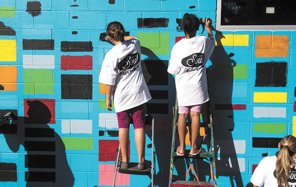 Gonzaga students paint a mural on a new nonprofit restaurant called Fresh Soul in the East Central neighborhood. The mural was designed by Spokane Arts Fund program manager Ellen Picken in collaboration with Spokane Arts, Fresh Soul and Gonzaga University. - RAJAH BOSE PHOTO