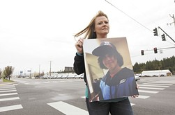 Carrie Thomson holds a picture of her son at the intersection where he was killed in 2014 - YOUNG KWAK