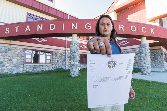 Jacob Johns, a Spokane resident and Gila River Pima tribal member, in front of the Standing Rock Sioux Tribe administration building, with a letter from the tribe asking the Spokane City Council to support efforts to stop construction of the pipeline. - JEFF FERGUSON