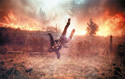 Gordon Maxwell dives over a fence as flames from Firestorm '91 rush towards him near Ponderosa in this award-winning photo by the late Kit King. Maxwell is a cook at a local restaurant. (Kit King / SR)