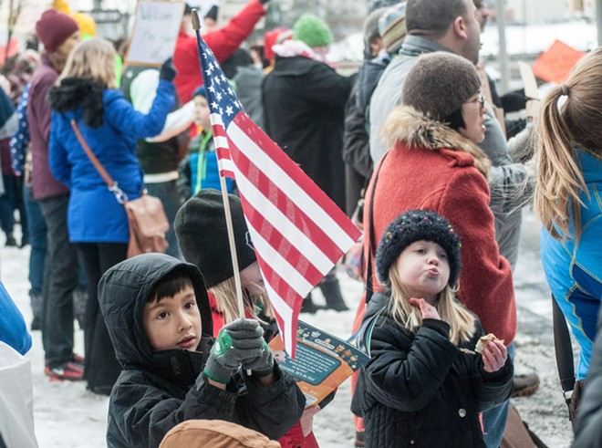 Children wave flags and read an Octonauts book at the protest of Trump's executive orders Sunday. - DANIEL WALTERS PHOTO