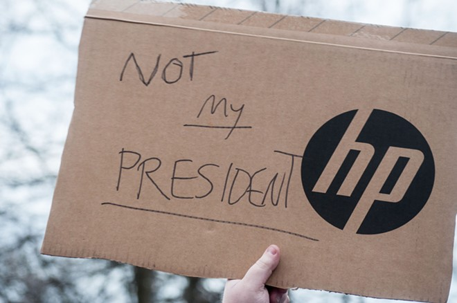 "A protester with ""NOT MY PRESIDENT"" written on the piece of a Hewlett-Packard box. - DANIEL WALTERS PHOTO"