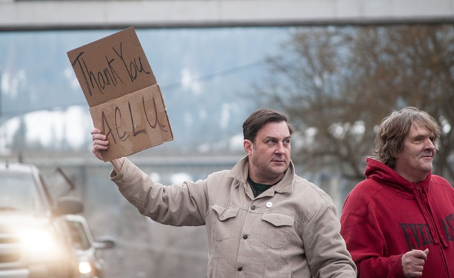 "City Council President Ben Stuckart holds a ""Thank You ACLU"" sign as he motions marchers to walk through the crosswalk next to local artist Hank Chiappetta. - DANIEL WALTERS PHOTO"