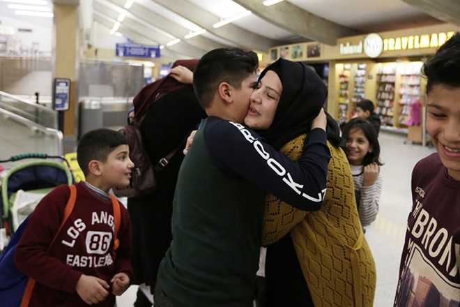 12-year-old Omar Kahiri a refugee from Iraq who arrived on a flight Saturday hugs his cousin Asma Abdul Almhos. - YOUNG KWAK PHOTO