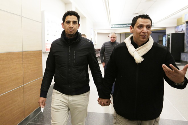 Newly reunited brothers Hamid Nahi and Assad Al-Sawaedi hold hands — an Arab gesture of intense friendship or platonic love — as they walk to the baggage claim. - YOUNG KWAK PHOTO