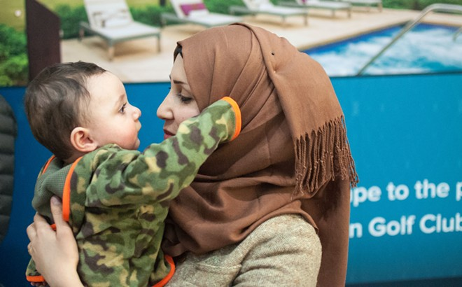 Moments after arriving in Spokane, Raghad Al-Sawaedi holds her nephew, Cannon Nahi, for the first time. - DANIEL WALTERS PHOTO