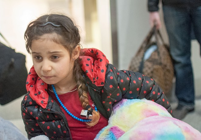 Iraqi refugee Rahaf Al-Sawaedi scopes out the Spokane airport while holding a brightly colored stuffed bear. - DANIEL WALTERS PHOTO