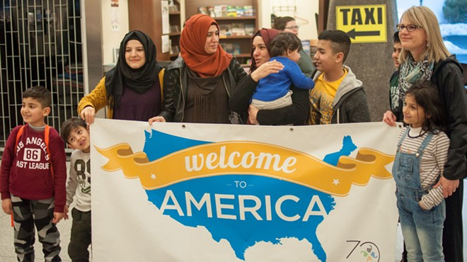 "A refugee family, reunited, poses with World Relief's Nancy Goodwin and a ""Welcome to America"" sign. - DANIEL WALTERS PHOTO"