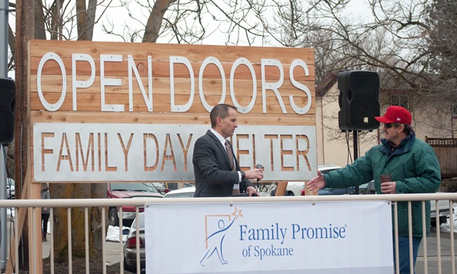 Steve Allen, executive director of Family Promise of Spokane, goes to shake a man's hand while preparing for a celebration of the recent opening of Open Doors daytime shelter for homeless families. - SAMANTHA WOHLFEIL