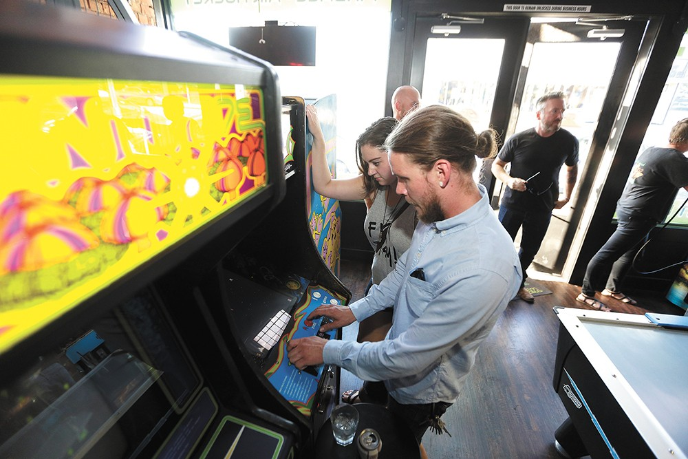 Christopher Anderson, right, plays Galaga as Samantha Seay watches at Gamers Arcade Bar. - YOUNG KWAK
