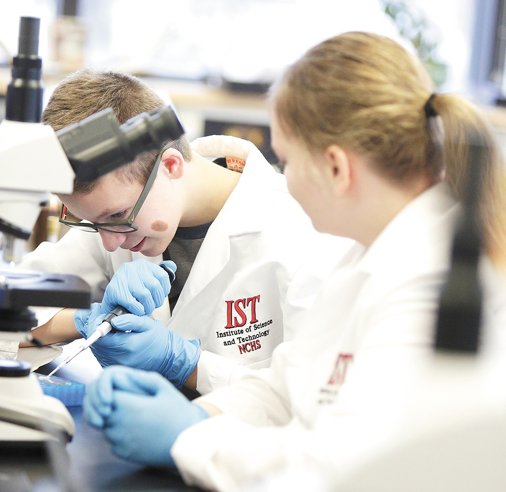 Andrew Liezen, 12, examines an E. coli sample in North Central's microbiology class. - YOUNG KWAK