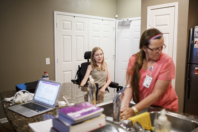 Frances Isbell looks on as personal care assistant Christy Robertson washes dishes and prepares food for her in Tuscaloosa, Ala., June 27, 2017. Isbell has spinal muscular atrophy and is finishing up law school at the University of Alabama. Optional benefits received by millions, many of them disabled, would be at risk under Republican proposals to repeal the Affordable Care Act. - MELISSA GOLDEN/THE NEW YORK TIMES