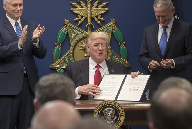 President Donald Trump holds up an executive order he signed at the Pentagon, where James Mattis, right, was also sworn in as defense secretary, in Arlington, Va., Jan. 27, 2017. Trump signed orders related to military spending and the vetting of immigrants. At left is Vice President Mike Pence. - STEPHEN CROWLEY/THE NEW YORK TIMES