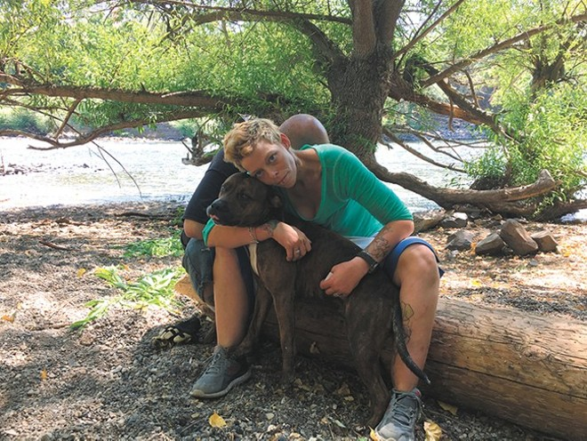 Destiny Brown, a homeless woman from Pennsylvania, and her dog Mister were forced to leave an area where she had been camping on the north bank of the Spokane River, below Kendall Yards. - MITCH RYALS PHOTO