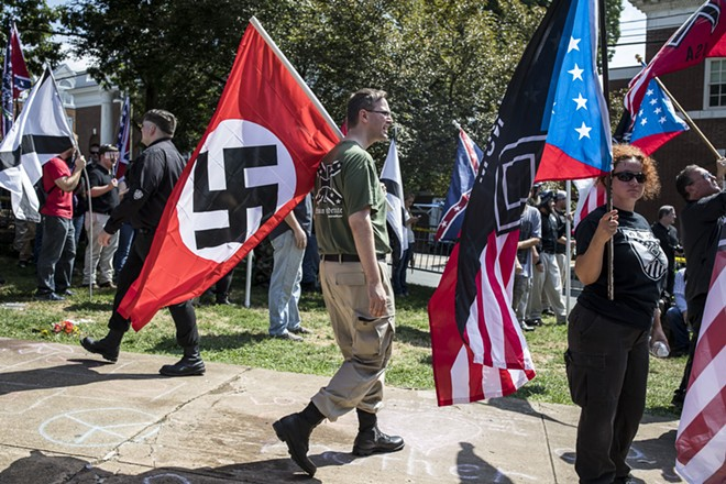 "A white nationalist carries a Nazi flag during a protest in Charlottesville, Va., Aug. 12, 2017. The White House, under siege over President Trump's initial comments, on Sunday condemned ""white supremacists"" for inciting violence that left a woman dead Saturday. - EDU BAYER/THE NEW YORK TIMES"