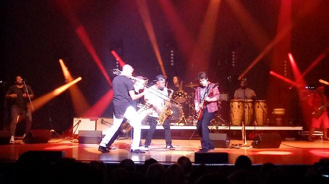 Trombone Shorty (left) and his sax men challenging guitarist Pete Murano to a musical showdown. - DAN NAILEN