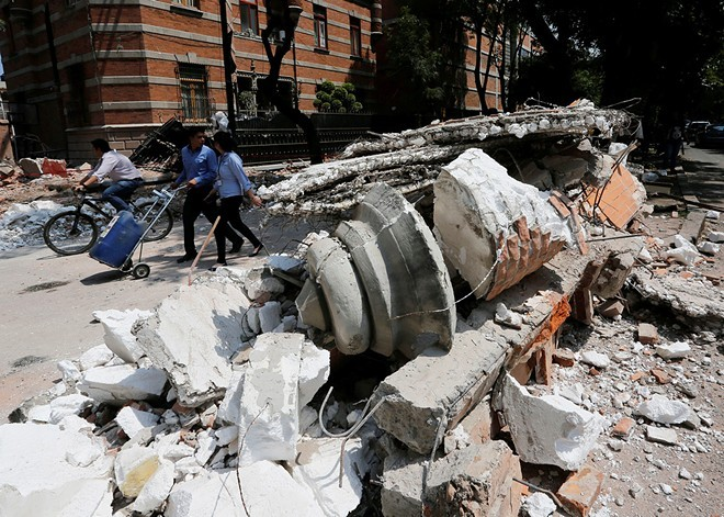 People in Mexico City walk past debris after an powerful 7.1 earthquake struck the metropolitan area of 21 million. - THE NEW YORK TIMES