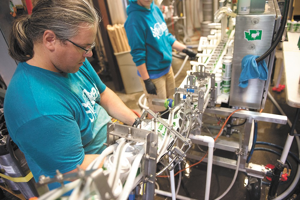 Isaac Joslin repairs the twist rinse, which sanitizes the cans. - DEREK HARRISON