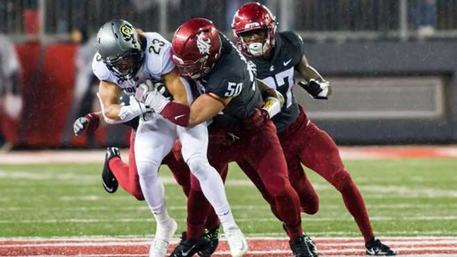 A swarming Cougar defense led by Hercules Mata'afa (50) held Colorado star Phillip Lindsay, who had rushed for nearly a thousand yards entering Saturday night's game at Martin Stadium, under 100 yards on a hard-fought 29 carries. - WSU ATHLETICS