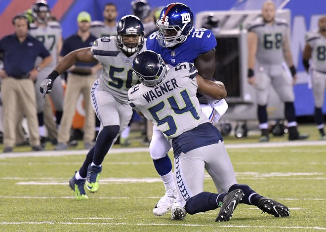 Bobby Wagner wraps up Giants running back Orleans Darkwa, while K.J. Wright closes in for the takedown. - SEAHAWKS.COM