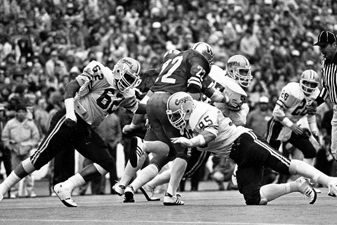 Three Washington State defenders surround Washington running back Sterling Hinds as Cougars safety Paul Sorensen (28) closes in on the play during the 1981 Apple Cup at Husky Stadium, won 23-10 by the UW. - WSU ATHLETICS
