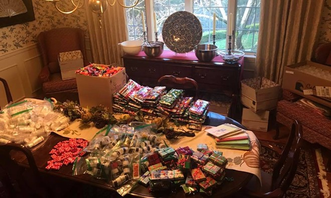 Volunteers who work with 300 Boodle Brigade-Spokane individually wrap needed items and gifts to send to deployed troops. - 300 BOODLE BRIGADE-SPOKANE