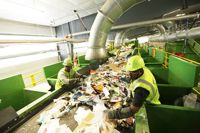 Presort Lead Jameel Henricksen, right, and Sorter Jerome Thomas remove plastic bags at Waste Management's SMaRT Center in Spokane. - YOUNG KWAK