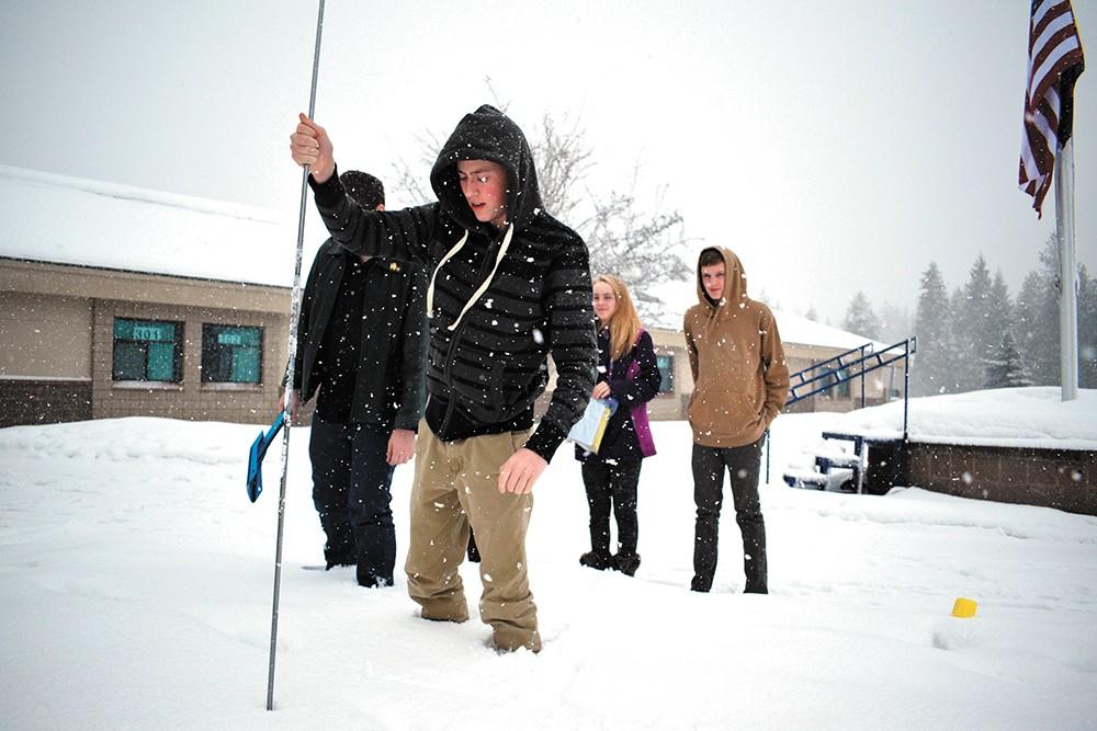 Timberlake High School sophomores Cheyenne Kiecker and Caleb Sorensen (right) watch classmate Logan Jones mark a spot to measure snowpack. - WILSON CRISCIONE