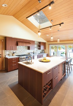 """""""People gravitate to the kitchen no matter what, but they don't have to be in the way,"""" says designer Sarah McGovern, who worked on this South Hill kitchen. The large island creates a functional barrier that still allows guests to interact with the cook. - JOE NUESS PHOTO"""
