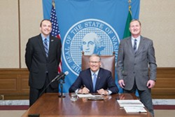 Marcus Riccelli, D-Spokane, and Jeff Holy, R-Cheney, celebrate Gov. Jay Inslee signing a bill to expand the Spokane County Commission. - COURTESY OF WASHINGTON HOUSE DEMOCRATS