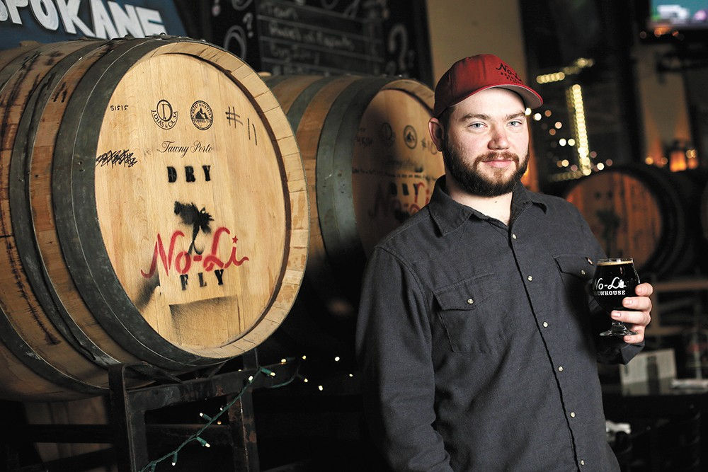 """No-Li head brewer Ryan Brookhart with a glass of """"Rip Van Winkle,"""" a whiskey barrel-aged imperial stout. - YOUNG KWAK"""