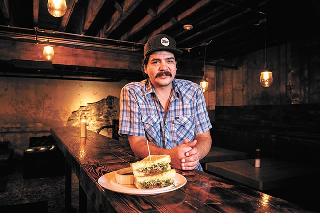 Chef CJ Callahan at Hogwash Whiskey Den with the bar's grilled cheese sandwich.
