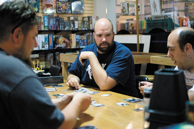 Mike Cline plans his next move while playing Arkham Horror at Uncle's Games. - STUART DANFORD