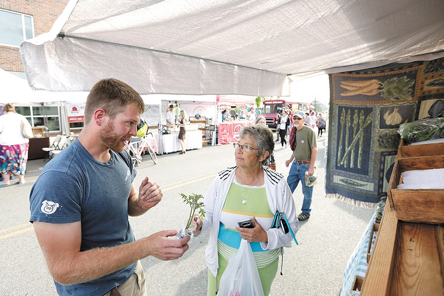 Woodard Family Farms owner Neil Woodard chats with a customer at the Kendall Yards Night Market. - YOUNG KWAK