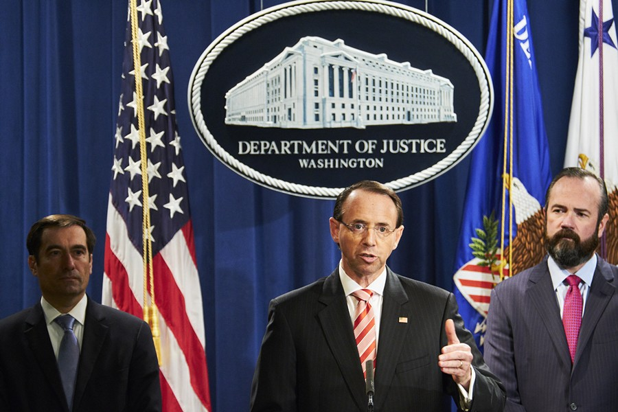 Deputy Attorney General Rod Rosenstein, center, at a news conference at the Justice Department in Washington, July 13, 2018. Rosenstein on Friday announced new charges against 12 Russian intelligence officers accused of hacking the Democratic National Committee and the Clinton presidential campaign. The announcement came just a few days before President Donald Trump is expected to meet with President Vladimir Putin of Russia in Finland. - T.J. KIRKPATRICK/THE NEW YORK TIMES