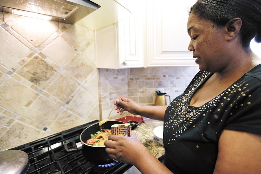 Kenyan native Jane Kamuasi prepares traditional mbuzi, a goat-based dish. - YOUNG KWAK