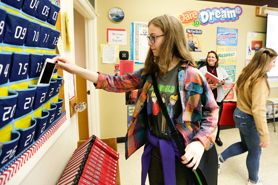 13-year-old Emelia Sanburn picks up her cell phone from a holder after class. - YOUNG KWAK