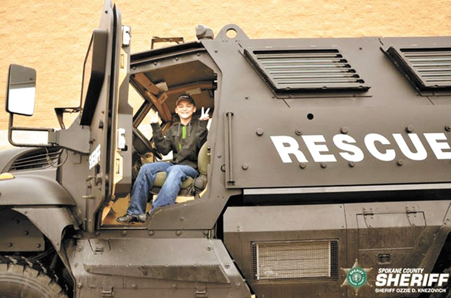 At December's Holidays and Heroes event, a boy sits in an MRAP vehicle some local critics see as police militarization.