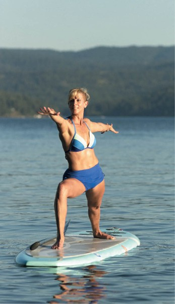 Kim Sherwood demonstrates a warrior pose on Lake Coeur d'Alene. - YOUNG KWAK