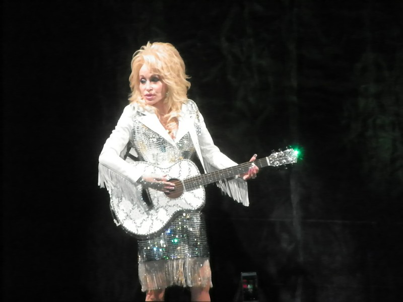 Guitar was just one of the instruments Parton played at her show Thursday night. - DAN NAILEN