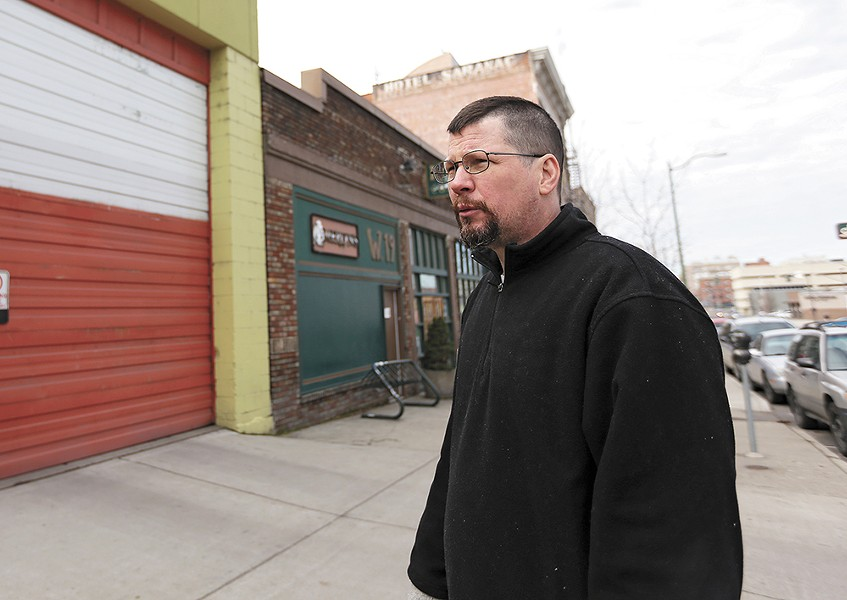 John Waite, owner of Merlyn's and Auntie's Bookstore, is counting on increased sales to make up for the cost of paying his employees more. - YOUNG KWAK