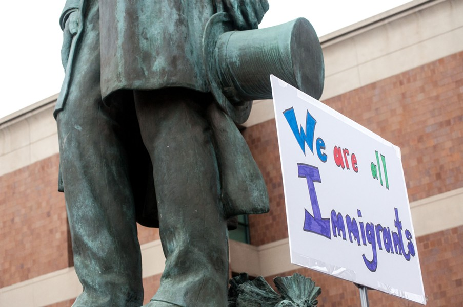 "A protester waves a ""we are all immigrants"" sign next to the Lincoln statue on Monroe street near downtown Spokane. - DANIEL WALTERS"