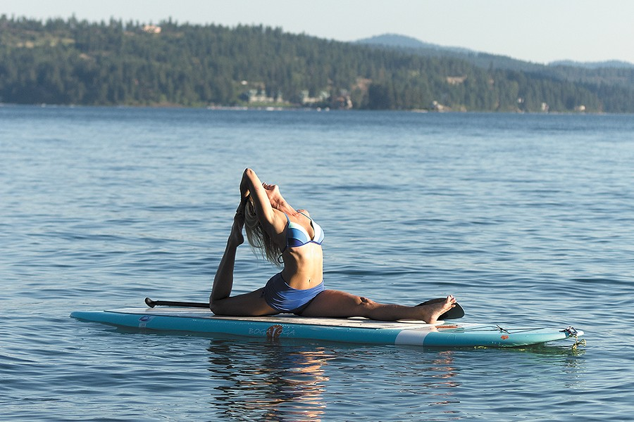 Kim Sherwood tests her balance and core strength with paddleboard yoga. - KWAK