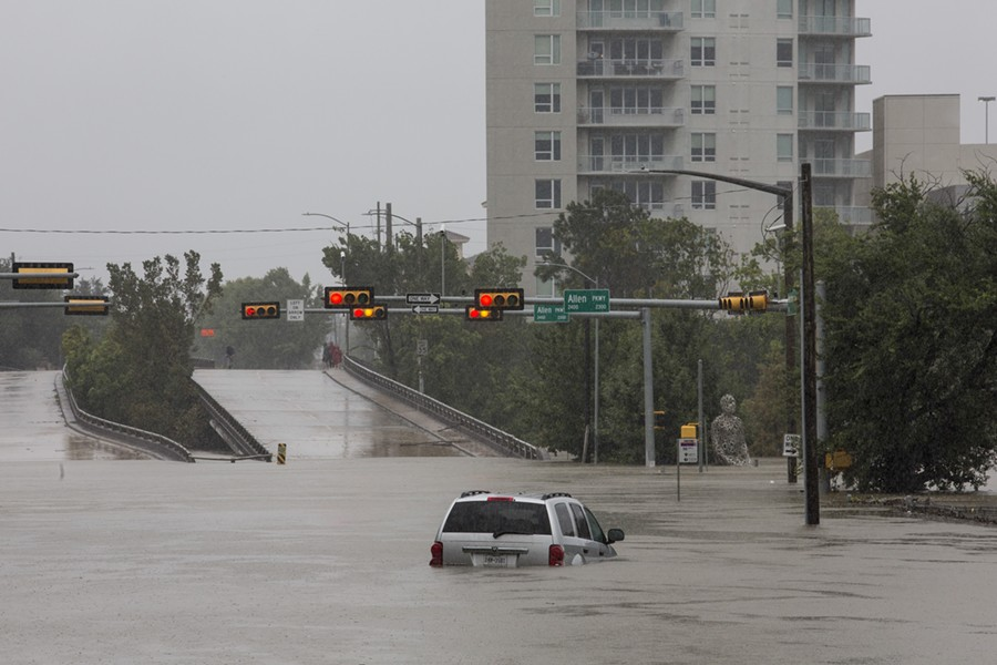 A car caught in the flooding along Buffalo Bayou and Allen Parkway in Houston, Aug. 28, 2017. With record floodwaters devastating much of southeast Texas, more than 450,000 people are likely to seek federal aid in recovering from Harvey, the storm that has battered the Gulf Coast for days, a Federal Emergency Management Agency official said. - SCOTT DALTON/THE NEW YORK TIMES