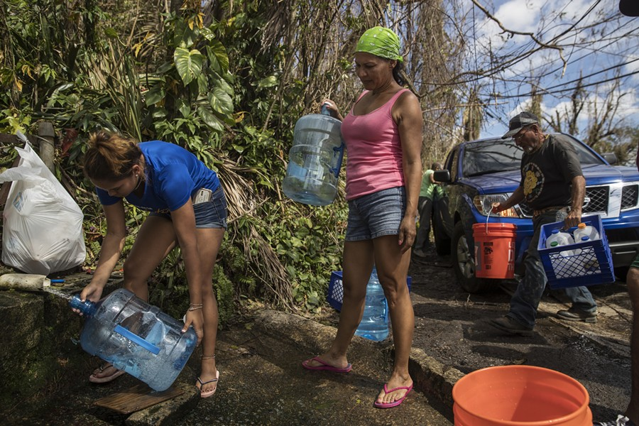 Luz Rosado, center, directs the filling of water vessels at a natural spring at her home in Toa Alta, Puerto Rico, Sept. 25, 2017. The Trump administration, which has insisted that its efforts in Puerto Rico were adequate, faced increasing pressure on Sept. 28 to mount a more aggressive response to Hurricane Maria's devastating lashing of the island. - VICTOR J. BLUE/THE NEW YORK TIMES