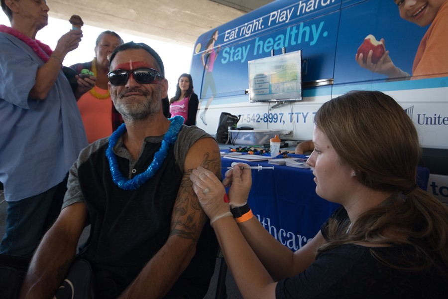 Walgreens volunteer Alacia Miller gives 48 year old Michael Bryan a flu shot in August 2017 at Blessings Under the Bridge's annual Luau in Spokane. - STUART DANFORD PHOTO