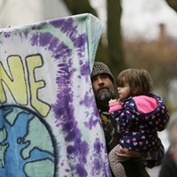 Peace Gathering and Fundraiser Joe Watts holds his 2 year old daughter Mia Rain while listening to a speaker. Young Kwak