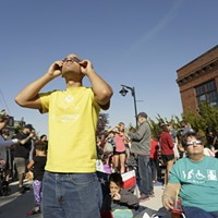 Partial Solar Eclipse in Spokane Steven Michell, left, his mother-in-law Jo-ann Button, left, look at a partial solar eclipse through solar glasses as his 7 year old son Eric Michell looks on, at the Spokane Tribal Gathering Place. Young Kwak