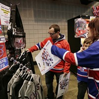 Kootenay Ice vs. Spokane Chiefs Damon Lentes, left, his fiancé Lauren Cox, right, and her 8 year old son Nathan Ennis look at Spokane Chiefs merchandise. Young Kwak
