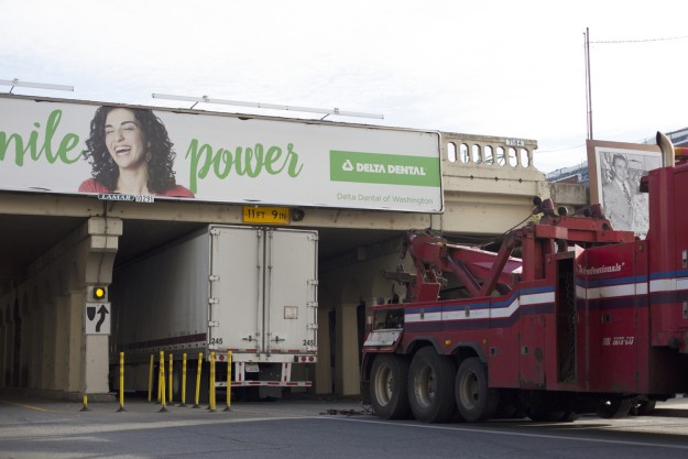 A tow truck attempts to yank out a semi-truck that got wedged under a bridge on Post Street downtown in September, as billboard woman chuckles at the truck driver's plight - YOUNG KWAK PHOTO